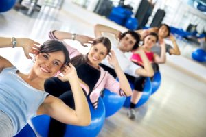 group of people at the gym smiling an doing abs exercises